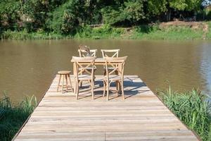 skrivbord och stol på en lång träbro nära floden foto