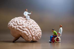 miniatyrkirurg som talar med en patient om hjärnskador, medicinsk vård och kirurgisk servicekoncept foto