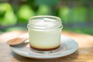 hemlagad karamell vaniljsås pudding i en glasflaska foto