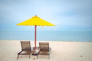 solstolar under ett gult paraply på stranden