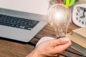 en man som håller en glödlampas växelsymbol medan han använder en dator foto