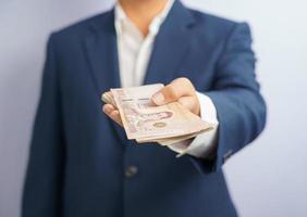 thailändska pengar i en företags mans hand
