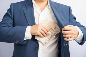 affärsman som håller thailändska pengar