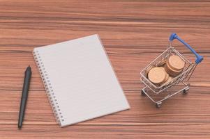anteckningsbok på skrivbordet med mynt i en liten vagn foto