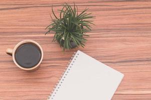 anteckningsbok på skrivbordet med kaffe och en växt foto