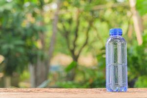 flaska dricksvatten med naturlig bakgrund foto