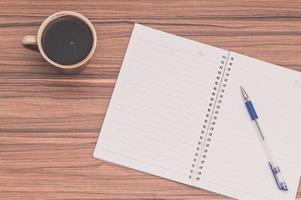 kaffe och ett anteckningsblock på träbord foto