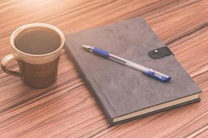 kaffe med ett anteckningsblock på träbord foto