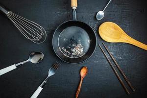 köksredskap och en svart stekpanna på svart bordsbakgrund