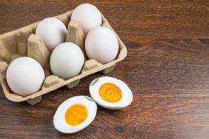 skivad hårdkokt ankaägg bredvid hela ägg i en kartong på ett träbord