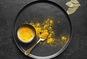 gult currypulver på en mörk bakgrund foto