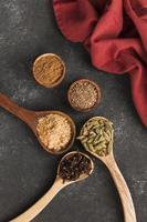 kryddor i skedar på en mörk bakgrund foto