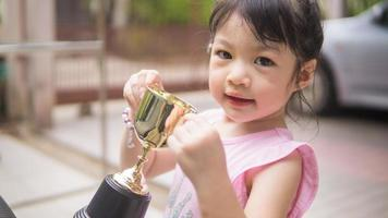 flicka som håller en trofé foto