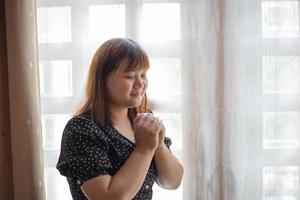 kvinna i bön nära ett fönster foto