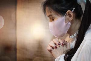 kvinna som ber med en mask på foto