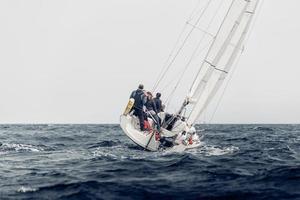 2019-- team som seglar regatta i dåligt väder foto