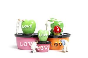 miniatyrmålare som färgar växter i en skida med ordet kärlek, alla hjärtans dagskoncept