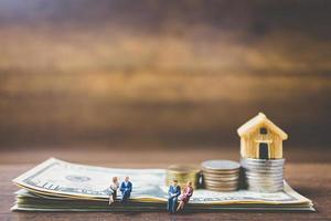 miniatyraffärsmän på pengar på en träbakgrund