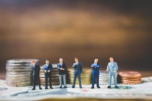miniatyraffärsmän på pengar på en träbakgrund foto