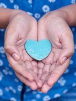 blå hjärta i händerna foto