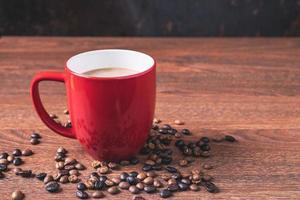 kaffe i en röd kaffekopp bredvid spillda kaffebönor på ett träbord foto