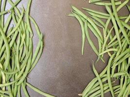gröna bönor på en mörk bordsbakgrund foto