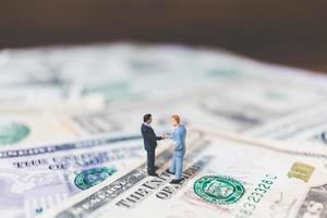 miniatyr affärsmän med oss dollar sedlar bakgrund