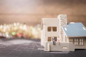 miniatyr människor som sitter hemma, investeringar och tillväxt i affärsidé foto