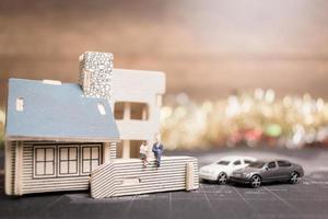miniatyrmänniskor som sitter hemma, investeringar och tillväxt i affärsidé foto