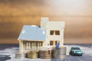 miniatyrfolk som sitter hemma med mynt, investeringar och tillväxt i affärsidé foto