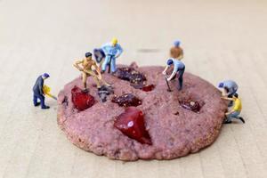 miniatyrbyggnadsarbetare på en jordgubbagrisrisbärkaka foto