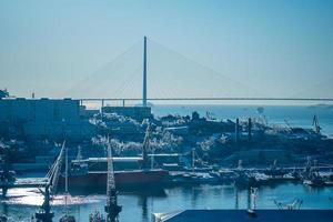 marinmålning med utsikt över en hamn och Russky-bron mot en klarblå himmel i Vladivostok, Ryssland foto