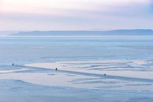 människor går längs isiga ytor med berg och molnig himmel i bakgrunden foto