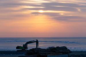 grävmaskin på en strand bredvid vattnet mot en färgglad molnig solnedgång i Vladivostok, Ryssland foto