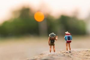 miniatyrresenärer med ryggsäckar som går på ett rock-, rese- och äventyrskoncept