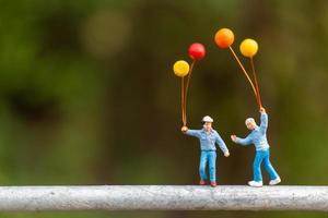 miniatyrfamilj som rymmer färgglada ballonger, lyckligt familjekoncept
