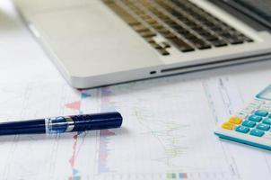 penna och miniräknare på dokument med bärbar dator foto