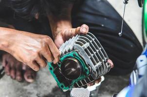 person som reparerar motorcykeln foto