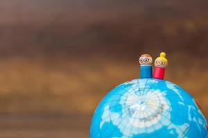 miniatyrträdockor på en jordglob med träbakgrund foto