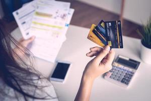 närbild kvinnans hand som håller tre kreditkort och papper vid ett skrivbord med miniräknare och en mobiltelefon