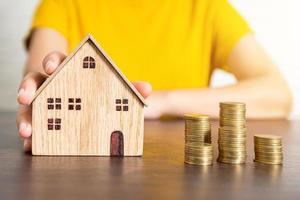 modell med gul skjorta som håller husmodellen bredvid högar av mynt