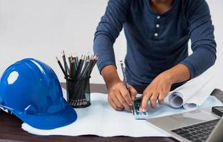 arkitekt som arbetar med en ritning bredvid bärbar dator, hjälm, pennor och rullat papper foto