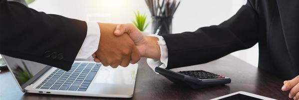 närbild av affärsmän som skakar hand bredvid en bärbar dator och en miniräknare foto