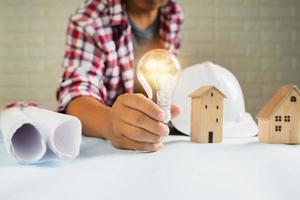 närbild av mans hand som håller tänd glödlampa bredvid husmodeller, hjälm och upprullade papper foto