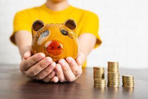 närbild av kvinna i gul skjorta som håller spargrisen bredvid högar av mynt foto