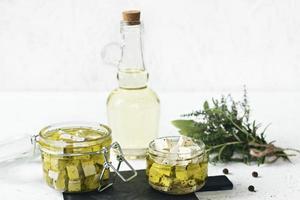 marinerad feta i en glasburk, kryddor och smaksatt olivolja på träbakgrund foto