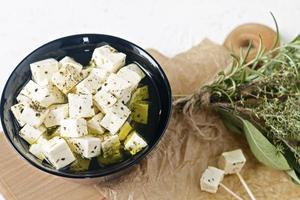 marinerad feta på en tallrik på en träskiva med kryddor på en vit bakgrund foto