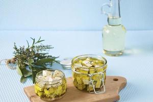 marinerad feta i en glasburk och kryddor mot en blå bakgrund foto