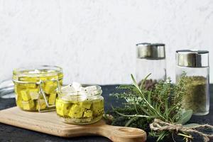 marinerad feta i en glasburk och kryddor mot en vit bakgrund foto