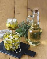 marinerad feta i en glasburk, kryddor och olivolja på träbakgrund foto